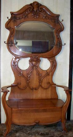 This is an exquisite example of an oak hall tree with lift seat.  The beveled glass mirror and HT hooks are both original.