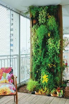 """Placas de fibra de coco (já vêm com os vasos fixados) formam o painel de 0,80 x 2,30 m, emoldurado em uma antiga viga de peroba. """"A desvantagem da fibra é que ela se desfaz com o tempo e a umidade. Por isso, exige manutenção constante e possíveis substituições a cada dois anos"""", explica Valter Carvalho, da Arte Viva, empresa de materiais de jardinagem de Diadema, SP. Aproveitando o desnível causado pela instalação do piso de demolição sobre o revestimento original do terraço, a paisagista…"""