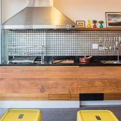 A cozinha de Mariela Cachuolo teve a parede da bancada revestida com mosaico de aço inox, trazendo modernidade em oposição à simplicidade elegante proporcionada pela mesa de madeira e banquinhos. #villabelarevestimentos #colormix #kitchen #decoração #design #designinteriores
