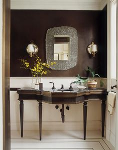 Dark and Glamorous  For a glamorous Manhattan apartment, designer David Kleinberg chose to continue a brass theme into the guest bathroom using a bronze-&-marble vanity; walls painted deep brown makes the small bath appear larger
