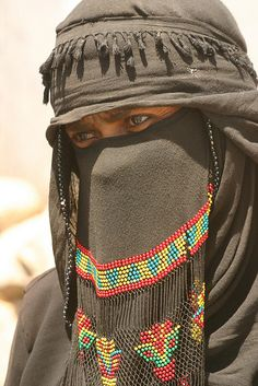 Veiled Yemeni woman in traditional clothes on the way in the mountains between Ma'rib and Sana'a. | © Walter Callens