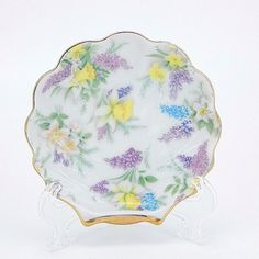 Vintage hand painted decorative collectible glazed ceramic shell shaped trinket dish.  The interior of the dish has a chintz floral design with purple and blue lilacs and yellow daffodil flowers with gold trim on the edges.  This dish would make a great ring or jewelry holder on a vanity, dresser or could be used by a bathroom or kitchen sink.  The small bowl could also be used as a teabag or tea spoon holder. #EverythingsCollectible #CollectItAll #TrinketDish #Lefton