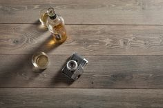 "Booze and camera! A great combo on our ""berg"" floors.  #stockholmcollection #maderatrade #scandinaviandesign #Scandinavianfloors #swedishfloors #whiteoakfloors"