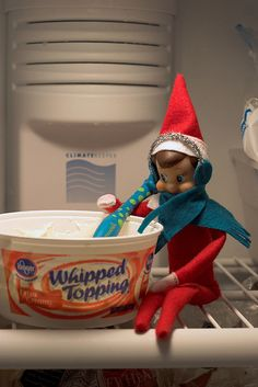 elf caught in the fridge with earmuffs and scarf