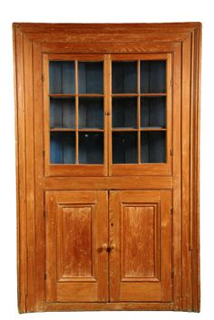 "COLONIAL PINE CORNER CUPBOARD - 18th c. Country Yellow Pine Cupboard with molded frame, six-light doors over two recessed panel doors, blue painted interior with 3 shelves, molded base. 84"" x 54"" x 38"". Natural finish with traces of old green paint."