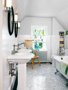 A sadly outdated—carpeted!—third-floor bath was gutted to create a boutique retreat for guests. Dual pedestal sinks keep the space feeling open and airy.   Photo: Gridley + Graves