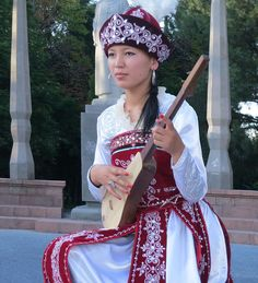 A Kyrgyz girl playing the stringed intrument called Komus. Bishkek, Kyrgyzstan.