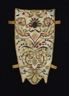 Stomacher | Museum of Fine Arts, Boston.  English, 1640-60.  Gray-white silk embroidered with polychrome silk and gilt-silver yarns in Baroque stylized vegetative motif. Gold silk grosgrain binding and four tabs at sides.