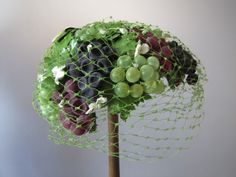 1950's wine grape cluster veil hat (side view) | Green partial face veil with the netting sprinkled with dots.  The cluster of grapes look as if they were just picked off the vine during the early morning dew. Little green velvet bow at the back