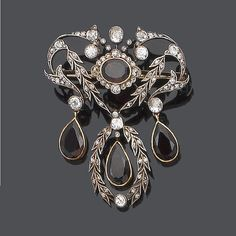 A diamond and garnet brooch/pendant The oval mixed-cut garnet within a scrolling foliate openwork plaque, set throughout with old brilliant, single and rose-cut diamonds, suspending three pear-shaped garnets, old brilliant and single-cut diamonds approx. 1.10ct. total, length 4.8cm