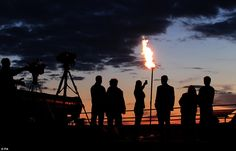 Incredible: People view the Diamond Jubilee beacon at Edinburgh Castle beside Mons Meg Cannon during the sunset