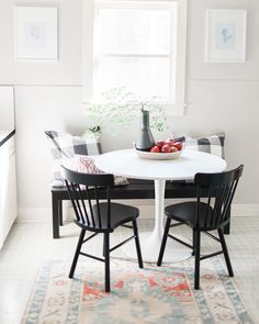 Dining nook in a rental kitchen, with white tulip table, traditional black shaker chairs and black banquet bench, and buffalo checked pillows, accessories by Studio McGee and vintage rug from The Southern Loom.