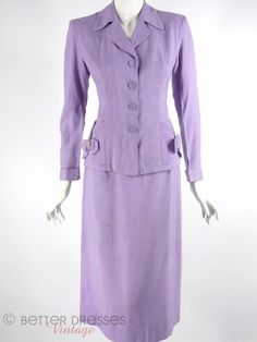 Late 1940s or early 1950s skirt suit is pretty in purple. Jacket features princess and elbow seams, four covered buttons, long cuffed sleeves, subtle shoulder p