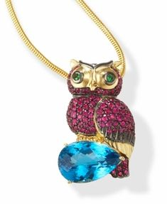 Ruby and Blue Topaz 18k Gold Owl Pendant - Make a statement with this 18kt Gold owl ring and pendant. It is sparkling with Rubies & green Garnet eyes. The owl is perched  on a magnificently crisp blue  Topaz stone. Removable Gold  band converts this ring into an  owl pendant - 2 magnificent  pieces of jewelry in one.  Breathtaking!  9.58 carat pear shape Blue Topaz gemstone. 2.44 ctw of Ruby stones.  07 ctw of Green Garnet (Tsavorite). •$2,995