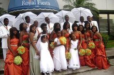 Burnt Orange with green sashes on the dresses -   Love the Groomsmen all in White and holding Umbrella's (Real Nice)