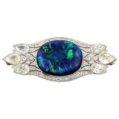 1930s Black Opal Diamond Platinum Brooch. A platinum Art Deco brooch with diamonds and a central Black-Opal cabochon.  Marked 950.