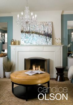 I gave this fireplace a fresh coat of Cloud White OC-130 paint then added a gas inset to solve the question of functionality.  The warm color of the leather ottoman balances the cool teal of the walls and a lovely area rug in muted tones of caramel and steely blue pull the whole room together.  #candiceolson
