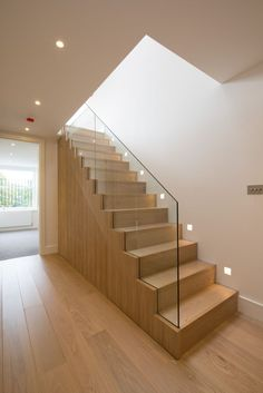 Oak staircase with frameless glass balustrade from hallway to upper level open plan living space.