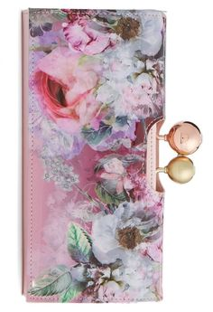 A gleaming kiss-lock clasp set with crystals highlights this leather Ted Baker wallet featuring a gorgeous floral print and a bevy of organizational pockets and card slots. On the #NSale.
