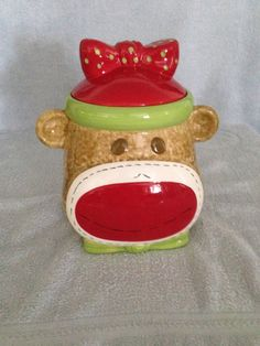 SOCK MONKEY COOKIE JAR REAL HOME GIRLWITH GIFT TAG This Real Home cookie jar is so cute! It is in like new condition (no chips, cracks, or crazing) and so charming. There are some letters written on the bottom of the piece but other than that she is in pristine condition. The bumper ring is...