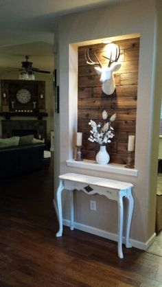 Wood wall, chalk painted table work added rustic hardware.....hubby's handiwork.   Deer head,  candles and flower arrangement....my design.   What a team!