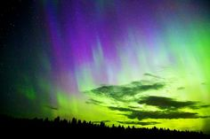 Glimmering green and blue auroras cover large swaths of sky above Canada