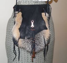 Fox fur and leather possibles bag  This bag is made with black deer skin leather and fox fur It measures 8 x 10 1/4 The narrow braided straps are 58 long and tie It is a two compartment bag It is decorated with an antiqued copper pendant,(adapter, concho), copper and glass beads and copper cones  This can be worn cross body, as a shoulder bag or around the waist Wear this to your next mountain man rendezvous, pow wow, or wear every day  Remember that not all colors appear the same on all…