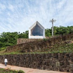 The expansive landscape of Argentina's Parque de la Cruz is the setting for this small chapel by Estudio Cella, which is elevated above the tree canopy in a forest clearing