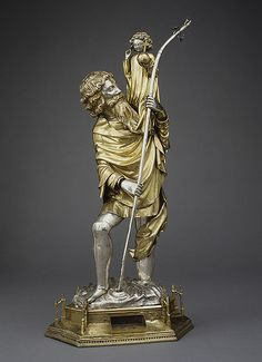 """Saint Christopher, 1400–1425French; Made in ToulouseSilver, silver-gilt 25 5/8 x 11 3/4 in. (65.1 x 29.9 cm)Gift of J. Pierpont Morgan, 1917 (17.190.361) @Dan Soule Venerated from the early centuries of Christianity, Saint Christopher—whose name means """"Christ-bearer""""—was honored as the protector of travelers. According to The Golden Legend, Christopher ferried a small child across a river. As he did so, the child's weight grew increasingly heavy. When Christopher"""
