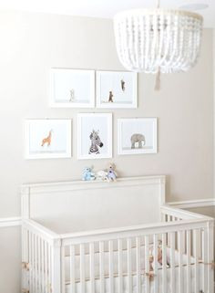Baby animals framed above crib in white #nursery with unique chandelier