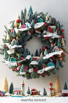 Escape into this tiny winter wonderland with tiny cardboard houses, frosted bottlebrush trees, miniature deer, and skiers all atop drifts of cotton snow. Recreate this cheerful holiday wreath with our step-by-step tutorial. #marthastewart #christmas #diychristmas #diy #diycrafts #crafts