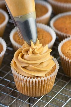 A swirl of caramel buttercream being piped onto a caramel cupcake.