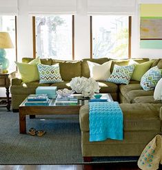 Love the sectional with the square coffee table in the center- so functional!  And the pop of turquoise!