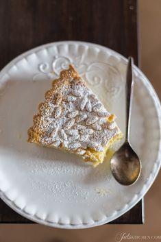 La torta della nonna ha un guscio di pasta frolla friabile e un ripieno denso di crema pasticciera, leggermente profumata di limone, il tutto coronato da una generosa manciata di pinoli e zucchero a velo.