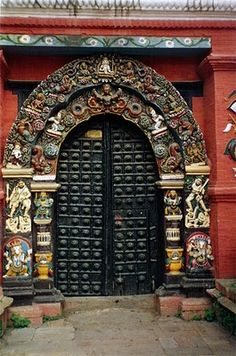 Carved decorative archway with black double doors in Kathmandu.
