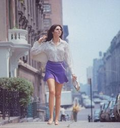 """Woman (possibly model), w. long hair wearing short skirt (mini skirt), lace top & sandals, walking up street, re story on """"New York look"""" in fashion.  Location:New York, NY, US  Date taken:1969  Photographer:Vernon Merritt Iii"""