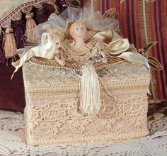 Beautiful heavy papermache square trinket or hat box that has been lavishly covered with a beautiful rose-beige moire fabric. The Bottom edge and top has been covered in hand tea stained venetian lace. Venetian lace has then been applied on the top as well along with tea stained sequined appliques, cording and fringe. It has been heavily decorated with satin wired ribbon along with silk roses, cording, fringe and pearl beads. A porcelain angel and hands has also been added to the top of the…