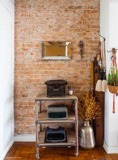 Essa hall de entrada tem tijolinhos e objetos étnicos adquiridos em viagens pelo mundo.
