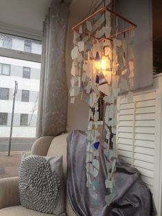 This glass chandelier is made from 100% recycled materials. Glass from gin and whisky bottles are combined with panes off broken windows and tumbled into