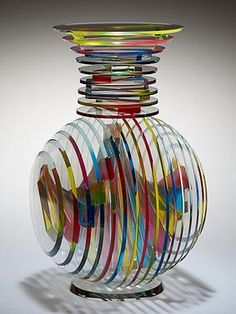 Sidney Hutter Vertical Vase laminated construction of cut and polished glass circles and polished bars. The bars are laminated in a helical pattern between the circles using a dyed, ultraviolet adhesive (red yellow & blue). Glass Bar, Art Of Glass, Blown Glass Art, Glass Artwork, Stained Glass Art, Fused Glass, Cut Glass, Clear Glass, Colored Vases
