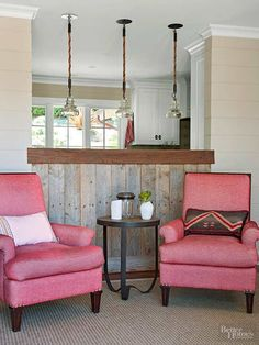 Reclaimed wood makes another appearance in the living room, highlighting the kitchen pass-through. A pair of plush pink upholstered chairs invite friends and family to take a seat and continue conversation.