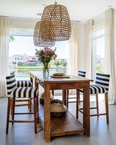 She chose to upholster the stools with this graphic striped fabric to balance the rustic nature of the table.