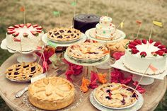 Wedding DIY: An Insanely Fun Old-Fashioned Carnival: A disheveled table filled with discarded flags, games, and empty drinks speaks volumes about the fun that was surely had. : A variety of pies and cakes are unified by mini flags created in the weddings color palette.