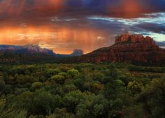 A light rain is illuminated by the rising sun over the mountains and valleys of the Southwest.