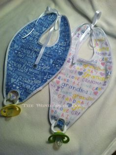 Baby bibs with pacifiers attached at the bottom.