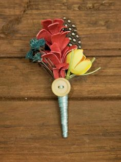 boutonniere.. i think all the flowers are fake but i love the colors and the feather. the red part reminds me of a painted pine cone. def a possibility :)