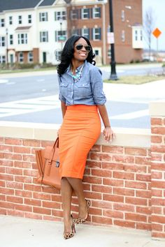 Pencil skirts don't have to be boring. A bright orange pencil skirt offset by a neutral like a chambray shirt play well together for a fun casual Friday combo.