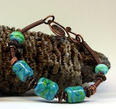 The beautiful Parakeet Bracelet is hand created with copper wire, coiled copper wire, 5 beautiful lampwork beads in colors of light and dark turquoise and pea green, copper accent beads, a hand created forged clasp. Fits up to a 7 1/2 inch wrist, jump rings can be added to make it fit a larger wrist. This will be a gorgeous handcrafted bracelet to add to your jewelry collection.