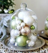 glass Christmas ornaments under a bell jar…