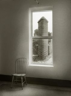 NYC. Flatiron Building through the window. Nice curved chair in contrast with the pattern of vertical and horizontal lines. // by Peter Liepke
